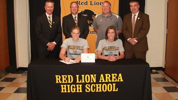 Amanda Myers signs with the Millersville track and field team. Seated next to her is Pamela Myers. Back Row: Arnie Fritzius, Director of Athletics;  Dr. Scott Deisley, Superintendent;  Jason Smith, Head Coach;  Mark Shue, Principal