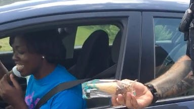 Officer Brian Warner of the Halifax, Va. Police Department hands over ice cream cones to the occupants of a vehicle he pulled over.