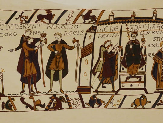 Bayeux Tapestry team members hang the tapestry in the