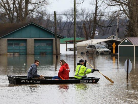 Scott Morrow paddles a boat to take family members