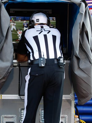 Referee Terry McAulay (77) watches a replay during a preseason game.
