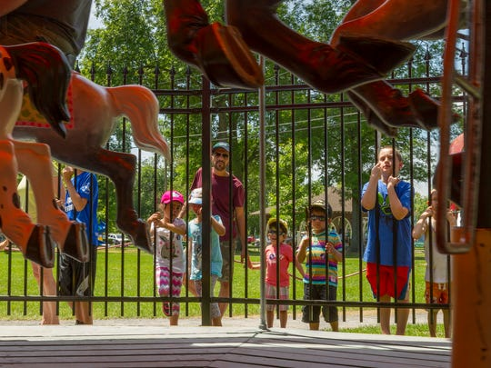 Children wait outside the new fence of the carousel in Stewart Park so they can take a turn riding on the 1951 amusement that was refurbished in 2014-2015.