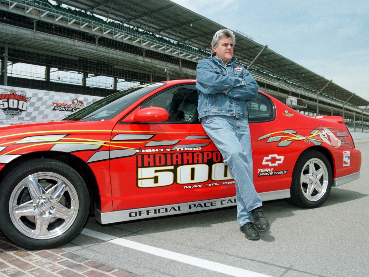 Comedian Jay Leno rests against the 2000 Monte Carlo pace car Tuesday he will drive this May in the 1999 Indianapolis 500 Mile race.
