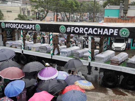 Trucks carry coffins with the remains of Chapecoense soccer team members who died in a plane crash, are taken to the team's stadium for a memorial in Chapeco, Brazil, Saturday, Dec. 3, 2016. The accident Monday in the Colombian Andes claimed most of the team's players and staff as it headed to the finals of one of Latin America's most important club tournaments.