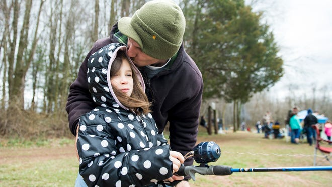 Travis Sterner kisses his daughter, Grace, 8, after helping her cast her line during an all-day youth fishing event at Kaiser Lake in New Oxford Saturday.