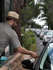 Emery Cowan/Arizona Daily Sun via AP, File Nate Powell, an employee with Grand Canyon National Park, collects an entrance fee as traffic is backed up as vehicles arrive at an entrance gate at Grand Canyon National Park, Ariz. Many of the country's most prominent national parks, including Grand Canyon, Yellowstone and Zion, set new visitation records in 2015.