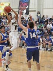 Menard High School's Noah Rosas gets ready to put up