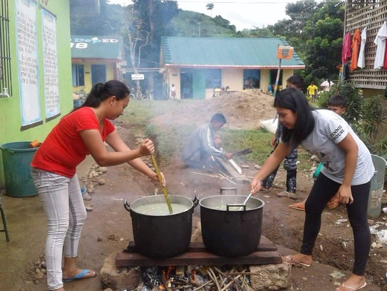 Two staff members prepare a meal for students. Along