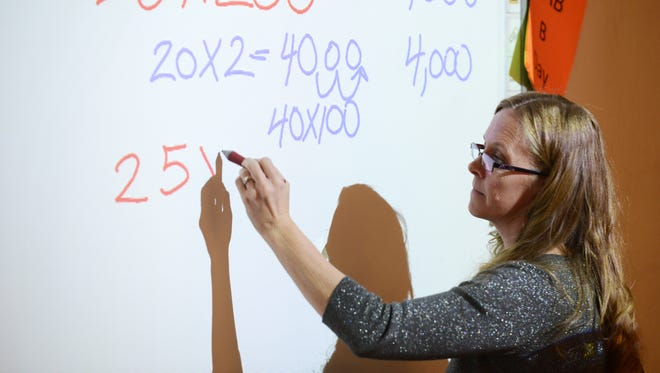 Zanesville High School math teacher Sabrina Penrose writes a problem on a SmartBoard during a recent math class. The lesson was an exercise in mental math, teaching students different ways to tackle a problem reach a correct answer.