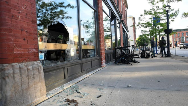 Broken glass litters the sidewalk outside Ember + Forge coffee shop in the 400 block of State Street in downtown Erie on May 31. CHRISTOPHER MILLETTE/Erie Times-News]