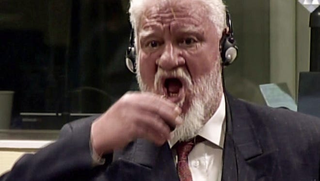 This video screengrab taken from live footage of the International Criminal Court, shows Croatian former general Slobodan Praljak swallowing what is believed to be poison, during his judgement at the U.N. war crimes court to protest the upholding of a 20-year jail term.