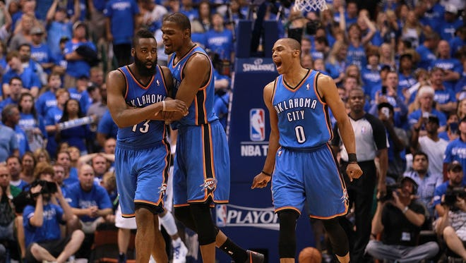James Harden, Kevin Durant and Russell Westbrook of the Oklahoma City Thunder celebrate after scoring with 10 seconds against the Dallas Mavericks during Game 4 of the Western Conference first round in the 2012 NBA Playoffs.