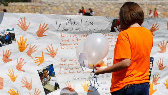"""Christina Cox, mother of Ty Cox reads  the posting by his classmates on the banner that was made to honor him Tuesday morning at an event held in h is honor. Cox a student at Mesa Vista Elementary School passed away last week after a six year battle with Histiocytosis, a rare disease characterized by an abnormal increase and acculilation of certain immune cells. His classmates held a balloon release, all wore orange shirts and ran a lap around the school playground in his honor as part of the """"Run Ty Run,"""" celebration."""