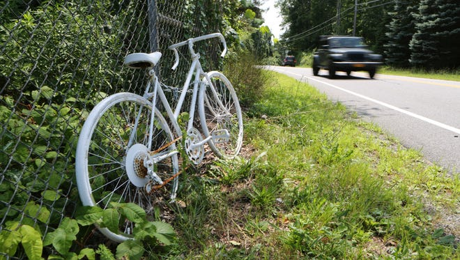 A parked bicycle by the side of a road.