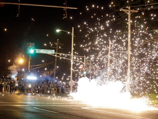 A device deployed by police goes off in the street as police and protesters clash Wednesday, Aug. 13, 2014, in Ferguson, Mo. Authorities in the St. Louis suburb where an unarmed black teen was shot and killed by a police officer have used tear gas to try to disperse protesters after flaming projectiles were thrown from the crowd. (AP Photo/Jeff Roberson) ORG XMIT: MOJR122