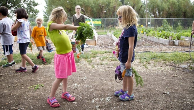 Macy Klostermeier, 6, left, shows carrots to friend McKenna Davison, 6, during lunch at the Westside Orchard Garden on Tuesday.