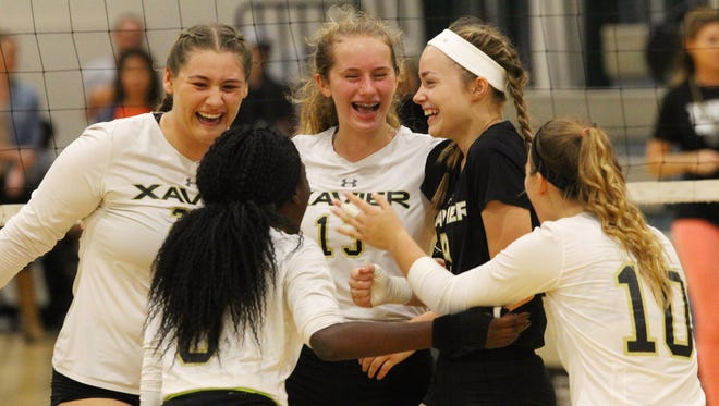 Xavier Prep Volleyball team celebrates winning the second set against J.W. North at home during their CIF first round match on October 31, 2017.