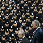 New York City Mayor Bill de Blasio, right, and NYPD police commissioner Bill Bratton, center, stand on stage during a New York Police Academy graduation ceremony on Monday, Dec. 29 at Madison Square Garden in New York. Mayor Bill de Blasio declares he has moved past the crisis with police that threatened to derail his administration. He says in an interview with The Associated Press that he was able to pull off the feat sticking to a strategy to maintain the moral high ground and avoid confrontation with police unions. At the same time, public opinion turned against police for their behavior in the feud, including turning their backs on the mayor.