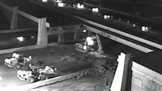 Contractors worked through the night to remove the damage section of the Rockville Road bridge over I-465.