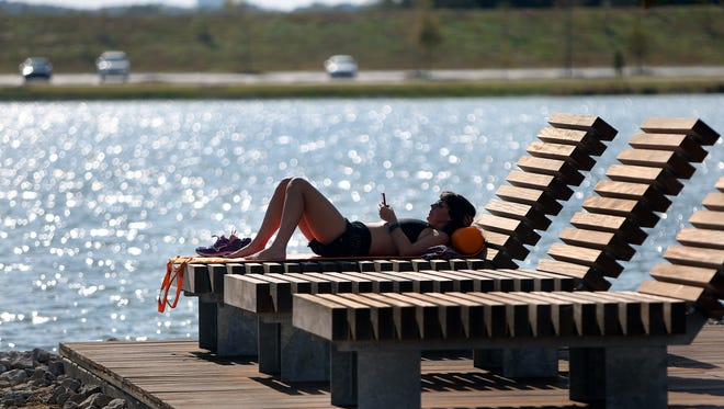 On an unseasonably warm day for October, Mary-Marsha Riley catches up on some reading at Patriot Lake, which Riley describes as a perfect place to enjoy some peach and quiet. The temperature peaked at 87, tying the record from 1984.