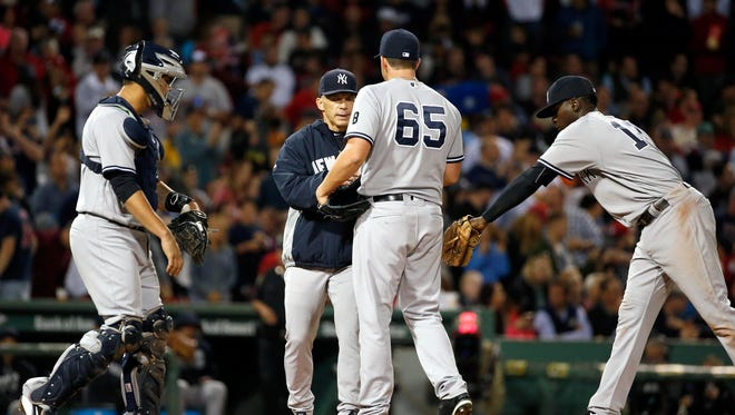 New York Yankees' Joe Girardi, center left, takes Jonathan Holder (65) out of the baseball game during the sixth inning against the Boston Red Sox in Boston, Friday, Sept. 16, 2016.
