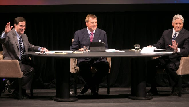 Fred DuVal (right) and Doug Ducey talk education with Fox moderator John Hook during the gubernatorial debate at Phoenix's Camelback High School auditorium on Sunday, Sept. 28, 2014.