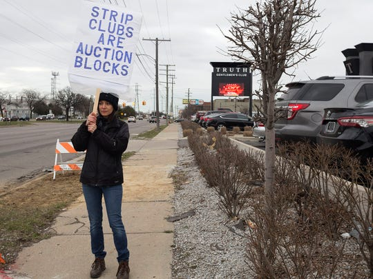 "Andrea Lavigne, 52, protests outside the Truth Detroit strip club before Stormy Daniels' ""Make America Horny Again"" tour on Wednesday, April 18, 2018 in Detroit. Lavigne is part of the Radical Feminists of Metro Detroit activist group."