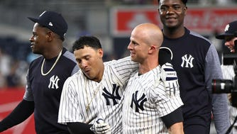 Yankees third baseman Ronald Torreyes (left) is congratulated by left fielder Brett Gardner (11) after hitting a walk off RBI single against the Texas Rangers during the tenth inning at Yankee Stadium on Friday, June 23, 2017.