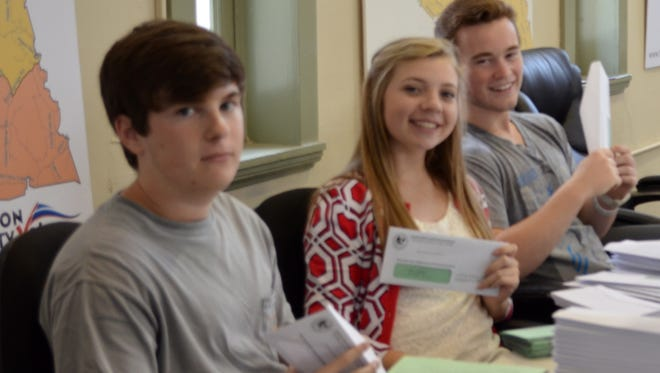 Cade Ramsey, left, Peyton Smith and Jonathan Luck prepare voter registration cards to be mailed out in Wilson County.