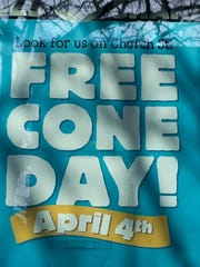 A sign in the window of the downtown Burlington Ben & Jerry's scoop shop, as seen on Sunday, April 2, 2017, encourages patrons to look for the company on Church Street on Free Cone Day.