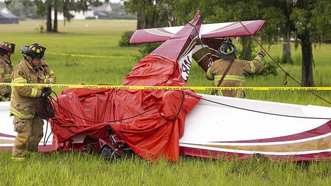 Marion County Fire Rescue firefighters work the scene of a fatal plane crash at Leeward Air Ranch on Wednesday.