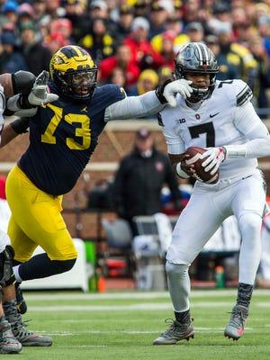 Michigan defensive lineman Maurice Hurst reaches for Ohio State quarterback Dwayne Haskins during the third quarter in Ann Arbor, Nov. 25, 2017.