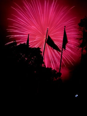The American flag is silhouetted against the fireworks display on Monday. America's Birthday Celebration at Gypsy Hill Park in Staunton was capped off with a fireworks show over Lake Tams on Monday, July 4, 2011.
