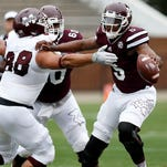Mississippi State Maroon squad quarterback Elijah Staley (5) tries to ward off a sack by Mississippi State White squad defensive lineman Nick James (88) during the first half of a spring NCAA college football game Saturday.