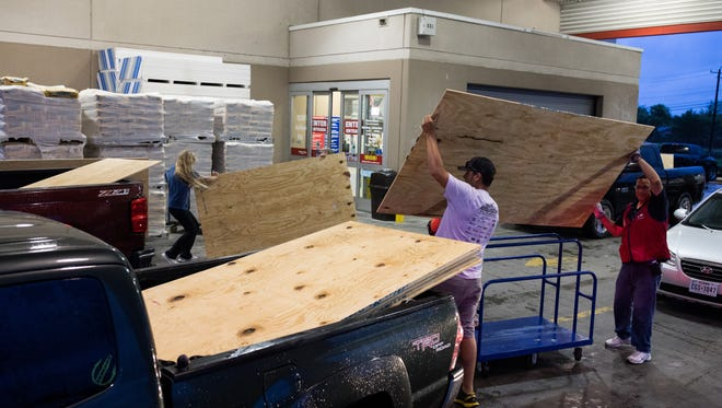 People load plywood in to their cars at a Lowes in Corpus Christi as Hurricane Harvey approaches, Aug. 25, 2017.