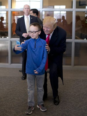 Donald Trump poses with a boy after a service at First Christian Church in Council Bluffs, Iowa, Jan. 31, 2016.