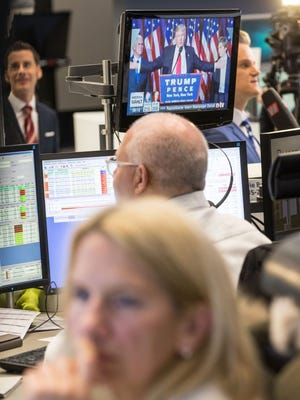 A televised speech of US President-elect Donald Trump is watched on a monitor in the background in the trade room of the Frankfurt Stock Exchange early Wednesday.