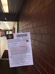 A UPS notice of inability to deliver a package clings to the window of Needler's located at 2250 Teal Road.