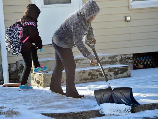 Antonia Hernandez sweeps lingering snow of the sidewalk