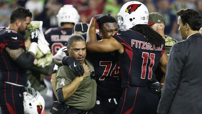 Arizona Cardinals Larry Fitzgerald hugs offensive tackle D.J. Humphries after suffering a knee injury against the Seattle Seahawks in the first half on Nov. 9, 2017 at University of Phoenix Stadium in Glendale, Ariz.