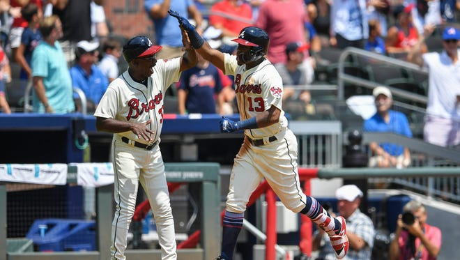 Braves leftfielder Ronald Acuna Jr. celebrates with third base coach Ron Washington after Acuna hit a two-run homer against the Brewers during the second inning at SunTrust Park on Sunday.