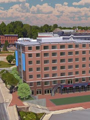 An artists rendering of a proposed hotel in downtown Winooski (center, with blue banners), shows its proximity to Main Street and the traffic circle.