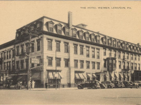 A postcard shows the Hotel Weimer on the southeast corner of Ninth and Cumberland streets in Lebanon. Automobiles are angle-parked along Ninth Street. The building has one chimney.