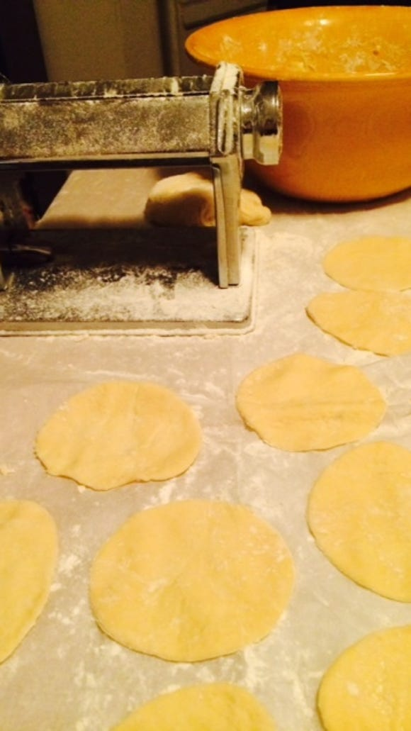 Rounds of dough await their allotment of potatoes and cheddar. The pasta maker helps move things along.
