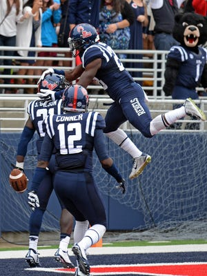 Mississippi defensive back Mike Hilton (28), right, and defensive back Tony Conner (12) celebrate with defensive back Senquez Golson (21) after Golson returned an interception for a touchdown during the second half of an NCAA college football game against Louisiana-Lafayette in Oxford, Miss., Saturday, Sept. 13, 2014. No. 14 Mississippi won 56-15. (AP Photo/The Daily Mississippian, Thomas Graning)