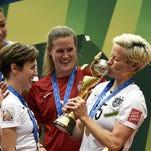 USA midfielder Megan Rapinoe (R) kiss the trophy next
