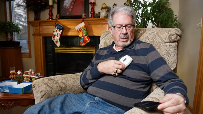 Glenn Milligan holds a sensor over the pacemaker in his chest which sends information to his smartphone app that uploads the information to the hospital Monday, Dec. 7 at his home.