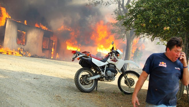 Dave Clark talks to neighbors on the phone as his house in Twin Pines burns in the Silver Fire on Wednesday, Aug. 7, 2013.