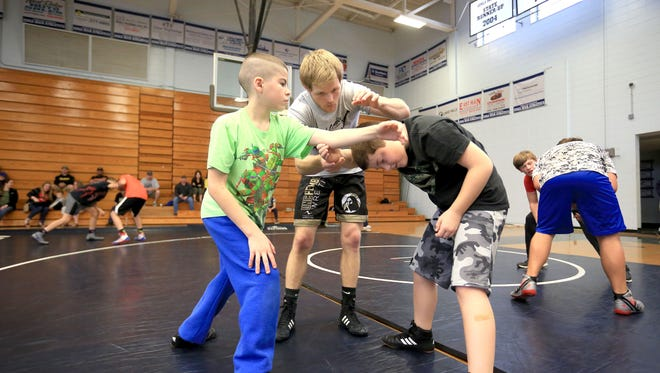 Daniel Ownbey demonstrates a move for Cody Jamerson, left, and Christian Lewis during his wrestling clinic on Saturday morning at Enka.