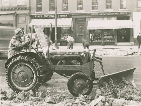 One of the new sidewalk plows cleaning ice and snow from Burlington's Main Street in March 1940. The plow pushed the ice and snow into windrows that were loaded into trucks by the rotary plow.